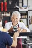 Cliente de Accepting Payment From do vendedor através do cartão de crédito imagem de stock