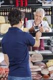 Cliente de Accepting Payment From do vendedor na loja do queijo imagem de stock royalty free