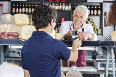 Cliente de Accepting Payment From do vendedor na loja do queijo fotografia de stock