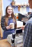 Cliente de In Cafe Serving da empregada de mesa com café afastado imagem de stock