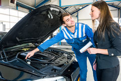 Cliente de Explaining Problems To del mecánico en garaje Foto de archivo libre de regalías