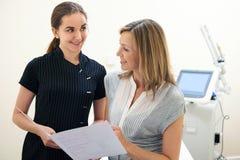 Cliente de femelle de Discussing Treatment With d'esthéticien photographie stock libre de droits