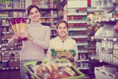 Cliente de femme avec la fille recherchant des pâtes dans le supermarché photos stock