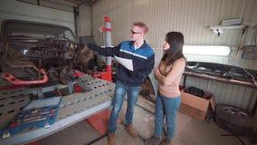Cliente de la demostración del mecánico el problema con el coche en el taller de reparaciones almacen de metraje de vídeo