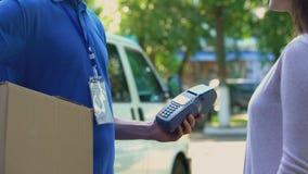 Cliente de la empresa de distribución que paga por el terminal sin contacto el transporte del paquete almacen de video