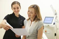 Cliente de la hembra de Discussing Treatment With del cosmetólogo Imágenes de archivo libres de regalías