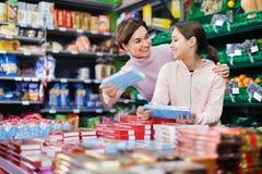 Cliente de la mujer con la muchacha que busca las galletas sabrosas Imágenes de archivo libres de regalías