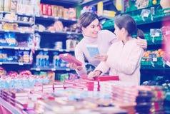 Cliente de la mujer con la muchacha que busca las galletas sabrosas Fotos de archivo