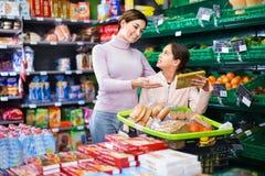 Cliente de la mujer con la muchacha que busca las galletas sabrosas Foto de archivo libre de regalías