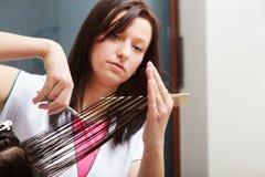 Cliente de la mujer del pelo del corte del peluquero en salón de belleza de la peluquería foto de archivo