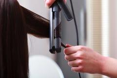 Cliente de la mujer del pelo del peluquero que se encrespa en salón de belleza de la peluquería Foto de archivo