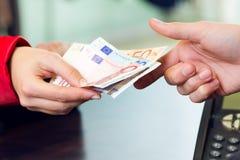 Cliente de la mujer que paga con el dinero Detalle de las manos Imagen de archivo