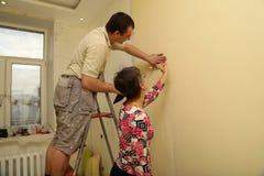 Cliente de la mujer y el trabajador que pone encima del papel pintado Imagenes de archivo