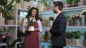 Cliente de ofrecimiento del florista lindo para comprar la planta en conserva metrajes