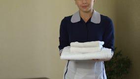 Cliente de ofrecimiento sonriente de la criada toallas blancas, servicio impecable en hotel de cinco estrellas almacen de video