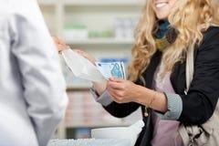 Cliente de Receiving Money From do farmacêutico para medicinas Fotografia de Stock