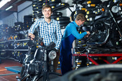 Cliente de riso do homem que guarda sua motocicleta fotografia de stock