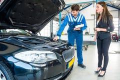 Cliente de Talking To Female del mecánico sobre el motor de coche Foto de archivo libre de regalías