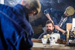 Cliente dei pantaloni a vita bassa che ottiene acconciatura Riflessione del barbiere che disegna capelli del cliente barbuto con  fotografie stock libere da diritti