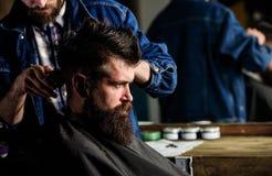 Cliente dei pantaloni a vita bassa che ottiene taglio di capelli Barbiere che disegna capelli del cliente barbuto con il pettine  fotografia stock