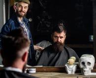 Cliente dei pantaloni a vita bassa e del barbiere con la barba che controlla taglio di capelli in specchio, fondo scuro Pantaloni fotografia stock