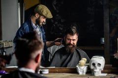 Cliente dei pantaloni a vita bassa e del barbiere con la barba che controlla taglio di capelli in specchio, fondo scuro Pantaloni immagine stock libera da diritti
