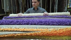 Cliente del giovane che seleziona la copertura del tappeto per la sua casa al centro commerciale 4k video d archivio