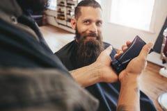 Cliente del servizio del barbiere al suo negozio fotografie stock