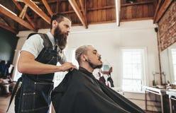 Cliente del servizio del barbiere nel salone di capelli fotografia stock