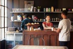 Cliente del servizio del personale in caffetteria occupata fotografia stock libera da diritti