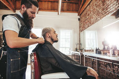 Cliente della copertura del barbiere con il capo del salone Immagine Stock