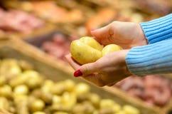 Cliente della donna che seleziona le patate fresche Fotografie Stock