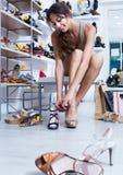 Cliente della ragazza che prova sulle scarpe scelte nel dipartimento delle calzature Immagini Stock