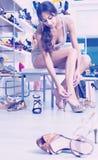 Cliente della ragazza che prova sulle scarpe scelte nel dipartimento delle calzature Fotografia Stock Libera da Diritti