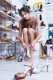 Cliente della ragazza che prova sulle scarpe scelte nel dipartimento delle calzature Fotografia Stock
