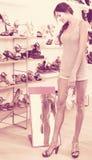 Cliente della ragazza che prova sulle scarpe scelte nel dipartimento delle calzature Immagine Stock