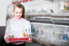 Cliente della ragazza che si vanta il suo acquisto dell'uccello color giallo canarino Immagini Stock Libere da Diritti