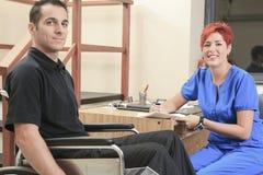 Cliente di aiuto della donna del fisioterapista al lavoro Fotografia Stock