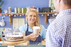 Cliente di In Cafe Serving della cameriera di bar con caffè Fotografia Stock Libera da Diritti