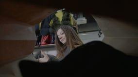 Cliente di modello femminile che esamina i vestiti di marca e che li mette in un sacchetto della spesa sul fine settimana regolar stock footage