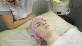 Cliente do esteticista que tem o procedimento de limpeza do vapor da cara termas, cosmetologia profissional video estoque