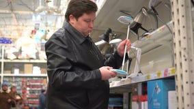Cliente do homem na loja que olha o candeeiro de mesa Escolhendo uma lâmpada de leitura para a família filme