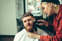 Cliente durante la barba che si rade nel negozio di barbiere immagini stock libere da diritti