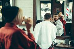Cliente durante la barba che si rade nel negozio di barbiere fotografie stock