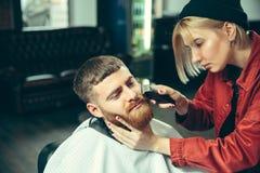 Cliente durante la barba che si rade nel negozio di barbiere immagine stock