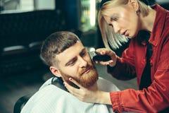 Cliente durante la barba che si rade nel negozio di barbiere fotografie stock libere da diritti