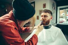 Cliente durante la barba che si rade nel negozio di barbiere immagini stock