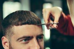 Cliente durante la barba che si rade nel negozio di barbiere fotografia stock libera da diritti
