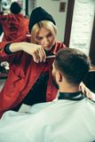 Cliente durante la barba che si rade nel negozio di barbiere immagine stock libera da diritti