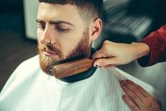 Cliente durante la barba che si rade nel negozio di barbiere fotografia stock